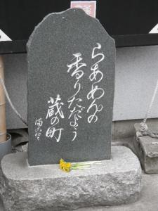 11050316まこと食堂・店舗前に佇む石碑