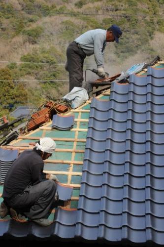 古民家の屋根瓦工事中の職人さん